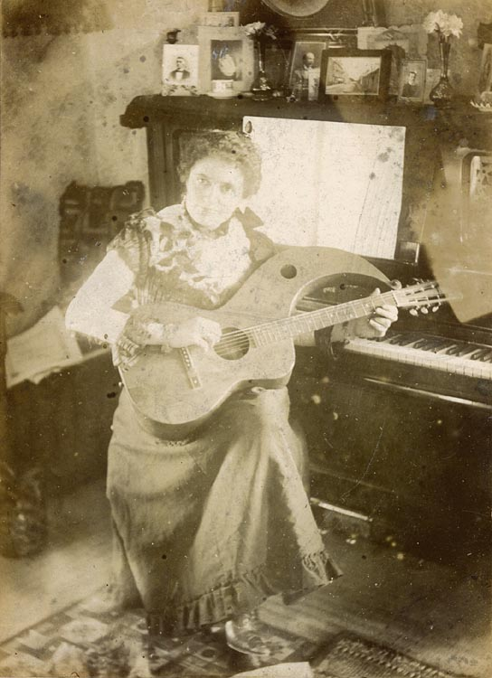 http://www.harpguitars.net/knutsen_images/knutsen-playing_woman-miner.jpg